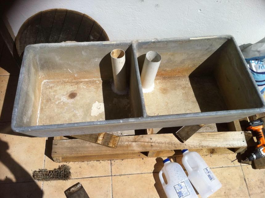 Concrete basin with drainpipes attached